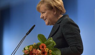 Chancellor and chairwoman of the German Christian Democrats, CDU, Angela Merkel, holds flowers after she was reelected as chairwoman with 96.7 percent during the 27th party convention in Cologne, Germany, Tuesday, Dec. 9, 2014. (AP Photo/Martin Meissner)