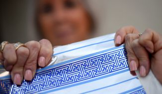 Cheryl Shapiro displays the Hanukkah gift wrap with a swastika-like pattern she found at Walgreens in Northridge, Calif., Monday, Dec. 8, 2014.  The wrapping paper has been recalled from stores nationwide. (AP Photo/Los Angeles Daily News, Andy Holzman)