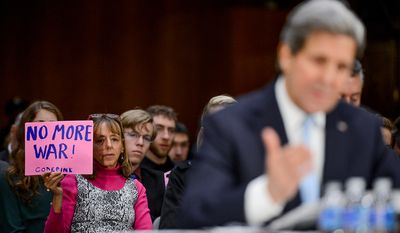 "A woman in the audience with the CodePink activists group holds a sign which reads ""No More War!"" as Secretary of State John Kerry testifies on the ""Authorization for the Use of Military Force Against ISIL"" in front of the Senate Foreign Relations Committee on Capitol Hill, Washington, D.C., Tuesday, December 9, 2014. (Andrew Harnik/The Washington Times)"