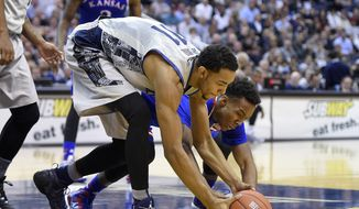 Kansas guard Devonte Graham, back, fights for a loose ball against Georgetown forward Isaac Copeland, front, during the first half of an NCAA college basketball game, Wednesday, Dec. 10, 2014, in Washington. (AP Photo/Nick Wass)
