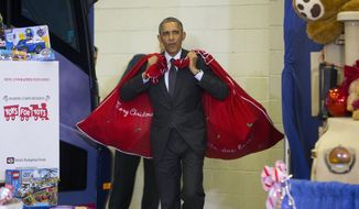 President Barack Obama carries two bags of gifts as he arrives to help first lady Michelle Obama sort toys and gifts for the Marine Corps' Toys for Tots Campaign, Wednesday, Dec. 10, 2014, at Joint Base Anacostia-Bolling in Washington. (AP Photo/Pablo Martinez Monsivais)