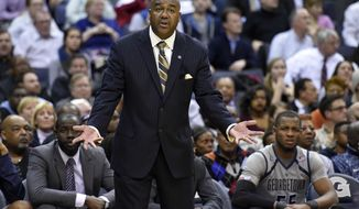 Georgetown head coach John Thompson III gestures during the second half of an NCAA college basketball game against Kansas, Wednesday, Dec. 10, 2014, in Washington. Kansas won 75-70. (AP Photo/Nick Wass)