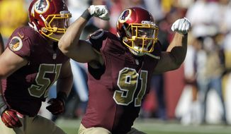 ADVANCE FOR WEEKEND EDITIONS, DEC. 13-14 - FILE -  In this Oct. 19, 2014, file photo, Washington Redskins linebackers Ryan Kerrigan (91) and Will Compton (51) celebrate Kerrigan's sack during the second half of an NFL football game against the Tennessee Titans in Landover, Md. For those who believe the guys who throw the football decide all NFL games, keep an eye on the guys who try to get those passers on the ground. (AP Photo/Mark E. Tenally, File)