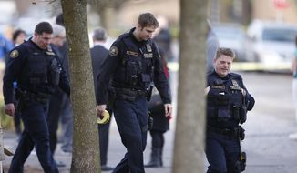 Portland Police near Rosemary Anderson High School, where a shooting took place Friday, Dec. 12, 2014. A shooter wounded two boys and a girl outside the high school Friday in what may be a gang-related attack, police said.(AP Photo/The Oregonian, Bruce Ely)
