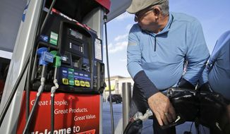 Eduardo Palacios-Paez, of Miami, pumps gas at a RaceTrac gasoline station, Thursday, Dec. 11, 2014, in Hialeah, Fla. Motorists are now seeing prices under $3 a gallon for the first time in four years, which also means that gas stations are paying less for the fuel, too. (AP Photo/Wilfredo Lee)