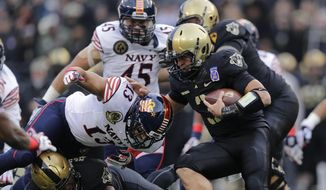 Army quarterback Angel Santiago, right, rushes the ball against Navy linebacker Jordan Drake (13) in the first half of an NCAA college football game, Saturday, Dec. 13, 2014, in Baltimore. (AP Photo/Patrick Semansky)