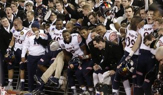 Navy players celebrate in the stands with Midshipmen after beating Army 17-10 in the Army-Navy NCAA college football game, Saturday, Dec. 13, 2014, in Baltimore. (AP Photo/Patrick Semansky)