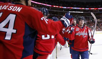 Washington Capitals center Nicklas Backstrom, right, from Sweden, celebrates his second goal in the second period of an NHL hockey game against the Tampa Bay Lightning, Saturday, Dec. 13, 2014, in Washington. Backstrom had a hat trick and the Capitals won 4-2. (AP Photo/Alex Brandon)