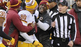 Washington Redskins wide receiver Santana Moss (89) is held back by teammates as he argues with a referee at the end of the first half against the New York Giants during an NFL football game, Sunday, Dec. 14, 2014, in East Rutherford, N.J. (AP Photo/Bill Kostroun)