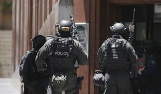 "Armed police stand at the ready close to a cafe under siege at Martin Place in the central business district of Sydney, Australia, Monday, Dec. 15, 2014. A hostage situation erupted inside a chocolate shop and cafe in Australia's largest city on Monday, with the nation's prime minister saying it may be ""politically motivated."" Television footage shot through the cafe's windows showed several people with their arms in the air and hands pressed against the glass, and two people holding up what appeared to be a black flag with white Arabic writing on it. (AP Photo/Rob Griffith)"