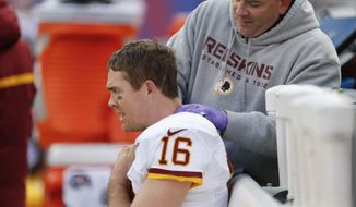 A trainer works on the neck of Washington Redskins quarterback Colt McCoy (16) during the second quarter of an NFL football game against the New York Giants, Sunday, Dec. 14, 2014, in East Rutherford, N.J. (AP Photo/Julio Cortez)