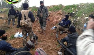 This Sunday, Dec. 14, 2014, photo provided by the anti-government activist group Syrian Observatory for Human Rights, which has been authenticated based on its contents and other AP reporting, shows Jihadi fighters from the al-Qaeda-linked Nusra Front and other rebel factions, rest after clashes with Syrian troops in Wadi Deif in the northwestern province of Idlib, Syria. (AP Photo/Syrian Observatory for Human Rights) ** FILE **