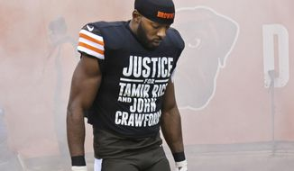 In this Dec. 14, 2014, photo Cleveland Browns wide receiver Andrew Hawkins wears a shirt calling attention to two black Ohioans killed during encounters with law enforcement before an NFL football game against the Cincinnati Bengals in Cleveland. The Browns say they respect the police and their player's rights to protest. (AP Photo/Tony Dejak)