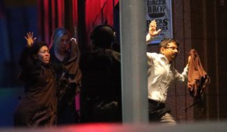 Hostages run towards armed tactical responce police as they run to freedom from a cafe under siege at Martin Place in the central business district of Sydney, Australia, Tuesday, Dec. 16, 2014. New South Wales state police would not say what was happening inside the cafe or whether hostages were being held. But television footage shot through the cafe's windows showed several people with their arms in the air.(AP Photo/Rob Griffith)