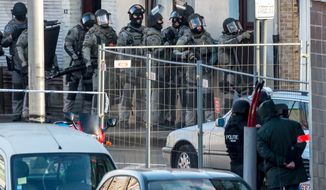 Special police forces prepare to invade an apartment block in Ghent, western Belgium, Monday, Dec. 15, 2014.  Belgian police detained three men after they took a hostage Monday in an apartment building in the western city of Ghent. The hostage was released unharmed. It was still unclear why the men had taken the hostage, but it was not an act of terror, federal police spokeswoman Annemie Serlippens said. (AP Photo/Geert Vanden Wijngaert)