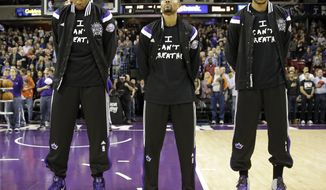 "FILE - In this Dec. 11, 2014, file photo, Sacramento Kings' Rudy Gay, left, Ramon Sessions, center, and Eric Moreland stand for the national anthem before an NBA basketball game against the Houston Rockets in Sacramento, Calif. Dozens of athletes in recent weeks have responded to confrontations between authorities and black citizens in Ferguson, Mo., New York and elsewhere by wearing T-shirts bearing such statements as ""I Can't Breathe"" and ""Hands Up, Don't Shoot!"" (AP Photo/Rich Pedroncelli, File)"