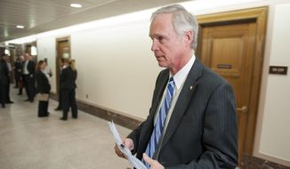 Sen. Ron Johnson, R-Wis., walks on Capitol Hill in Washington, in this Tuesday, April 1, 2014, file photo. (AP Photo/Cliff Owen, File)