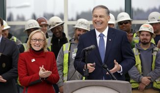 Gov. Jay Inslee, right, smiles as he stands with state Transportation Secretary Lynn Peterson and construction workers as he begins to take questions at a news conference Tuesday, Dec. 16, 2014, in Medina, Wash. Inslee, speaking from a spot overlooking the new floating bridge under construction on Lake Washington, announced his 12-year, $12 billion plan for rebuilding the state's transportation infrastructure. He said a third of the cost will be covered by a new tax on carbon pollution. The governor expects the state to collect $400 million a year from the state's worst polluters. Other expected sources of income for transportation include nearly $4 billion in tolls and other fees, plus more than $3 billion in construction bonds. (AP Photo/Elaine Thompson)