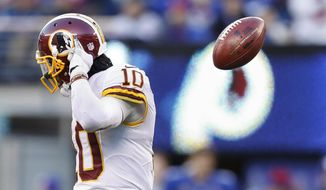 Washington Redskins quarterback Robert Griffin III (10) flips the ball back to the referee as he walks to the sidelines during the fourth quarter of an NFL football game against the New York Giants, Sunday, Dec. 14, 2014, in East Rutherford, N.J. (AP Photo/Julio Cortez)