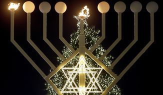 The first flames of a giant Hanukkah Menorah in front of a Christmas tree at the Brandenburg Gate in Berlin, Germany, Tuesday, Dec. 16, 2014 burn at the launch of the eight-day Jewish Festival of Lights, named Hanukkah. (AP Photo/Michael Sohn)
