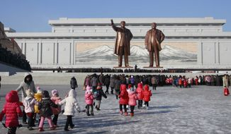 North Koreans gather at the Mansu Hill where the statues of the late leaders Kim Il Sung, and Kim Jong Il tower over them Tuesday, Dec. 16, 2014, in Pyongyang, North Korea, a day before the 3rd anniversary of the death of Kim Jong Il. (AP Photo/Wong Maye-E)