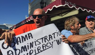 Protesters outside of Cafe Versailles on Calle Ocho in Miami,  decry the exchange of convicted Cuban spies, Wednesday, Dec. 17, 2014,  for USAID subcontractor Alan Gross, who has been held by the Cuban government. (AP Photo/El Nuevo Herald, Roberto Koltun)  MAGS OUT