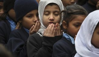 Pakistani students pray during a special ceremony for the victims of Tuesday's school attack in Peshawar, at a school in Lahore, Pakistan, Wednesday, Dec. 17, 2014. (AP Photo/K.M. Chaudary) ** FILE **