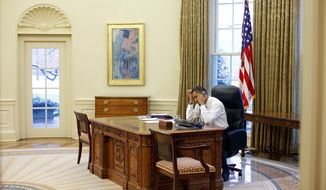 President Barack Obama talks on the phone in the Oval Office, Jan. 28, 2009.