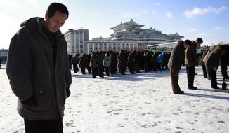 North Koreans gather at the Kim Il Sung Square, some bowing toward portraits of their late leader Kim Jong-il, as an act of respect, to mark the third anniversary of his death, Wednesday Dec. 17, 2014, in Pyongyang, North Korea. (AP Photo/Jon Chol Jin)