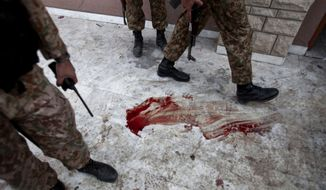 Pakistan army soldiers stand outside the auditorium of an Army Public School a day after an attack on the school, in Peshawar, Pakistan, Wednesday, Dec. 17, 2014. (AP Photo/B.K. Bangash)