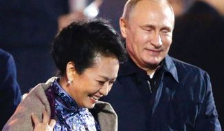 Russia's President Vladimir Putin, right, puts a shawl on Peng Liyuan, the wife of Chinese President Xi Jinping, at the Asia-Pacific Economic Cooperation (APEC) summit in Beijing, Nov. 10, 2014. (Associated Press) ** FILE **
