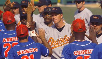 FILE - In this March 28, 1999 file photo, Baltimore Orioles pitcher Mike Timlin, center, and teammates are congratulated by the Cuban national team following the Orioles' 3-2 win in extra innings in Havana, Cuba. The exhibition game was the first time a Major League team has played in Cuba since the Cuban Revolution in 1959. The announcement on Wednesday, Dec. 17, 2014 that the U.S. plans to restore diplomatic ties with the Caribbean nation could usher in a new era in U.S.-Cuba baseball relations, which were strained after the Castro revolution and the U.S.-led economic embargo. (AP Photo/John Moore, File) ** FILE**