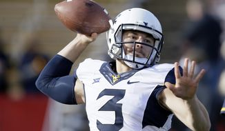 FILE - In this Nov. 29, 2014, file photo, West Virginia quarterback Skyler Howard warms up before an NCAA college football game against Iowa State in Ames, Iowa. West Virginia coach Dana Holgorsen says quarterback Clint Trickett has been cleared to play in the Liberty Bowl after being sidelined with a concussion in late November and missing the Mountaineers' regular-season finale. (AP Photo/Charlie Neibergall, File)