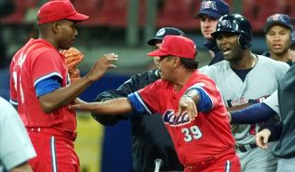 FILE - In this Sept. 23, 2000 file photo, Cuba's manager Servio Borges (39) keeps pitcher Jose Ibar, left, and United States batter Ernie Young separated after Ibar hit Young in the back in the fourth inning during the Olympic baseball competition at Sydney Olympic Park. The U.S. defeated favorite Cuba 4-0 in the gold medal game at the 2000 Sydney Olympics. The announcement on Wednesday, Dec. 17, 2014 that the U.S. plans to restore diplomatic ties with the Caribbean nation could usher in a new era in U.S.-Cuba baseball relations, which were strained after the Castro revolution and the U.S.-led economic embargo.  (AP Photo/Eric Gay, File)