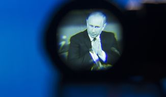 Russian President Vladimir Putin seen gesturing in a camera viewfinder during his annual news conference in Moscow, Russia, Thursday, Dec. 18, 2014. (AP Photo/Pavel Golovkin)