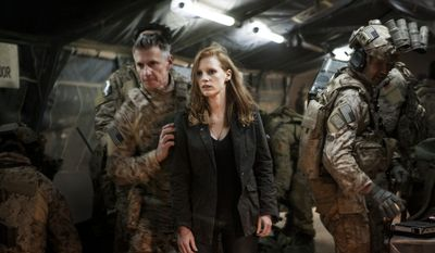 "Stationed in a covert base overseas, Jessica Chastain (center) plays a member of the elite team of spies and military operatives (Christopher Stanley, left, and Alex Corbet Burcher, right) who secretly devoted themselves to finding Osama Bin Laden in Columbia Pictures' electrifying new thriller directed by Kathryn Bigelow, ""Zero Dark Thirty."""