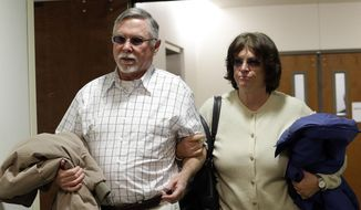 In this March 12, 2013, file photo, Robert and Arlene Holmes, the parents of Aurora theater shooting suspect James Holmes, arrive at district court for the arraignment of their son in Centennial, Colo. Jury selection is scheduled to begin in January 2015, for the 2012 attack in Aurora that killed 12 people and injured 70. (AP Photo/Ed Andrieski, File)
