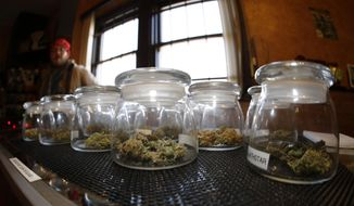Glass jars containing various strains of marijuana sit on a counter as sales associate Mattt Hart works at the 3D Dispensary on Friday, Dec. 19, 2014, in Denver. (AP Photo/David Zalubowski) ** FILE **