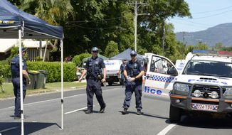Police patrol near a house where eight children have been found dead in a Cairns suburb in far north Queensland, Australia, Friday Dec 19, 2014. Queensland state police said they were called to the home in the Cairns suburb of Manoora on Friday morning after receiving a report of a woman with serious injuries. When police got to the house, they found the bodies of the children inside, ranging in age from 18 months to 15 years.(AP Photo/Graeme Bint)
