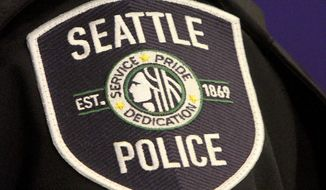 Seattle Police Department Officer Officer Debra Pelich shows the department's new uniform, which includes a newly designed shoulder patch, during a news conference in Seattle on Thursday, Dec. 18, 2014. (AP Photo/The Seattle Times, Greg Gilbert) ** FILE **