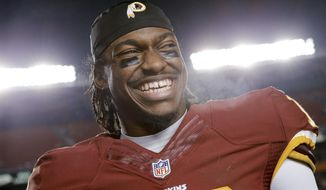 Washington Redskins quarterback Robert Griffin III smiles on the sideline after the Redskins defeated the Philadelphia Eagles 27-24 in an NFL football game Saturday, Dec. 20, 2014, in Landover, Md. (AP Photo/Patrick Semansky)