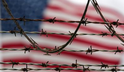 In this Oct. 10, 2007, file photo, reviewed by the U.S. Military, an American flag flies behind the barbed and razor-wire at the Camp Delta detention facility, at Guantanamo Bay U.S. Naval Base, Cuba. (AP Photo/Brennan Linsley)
