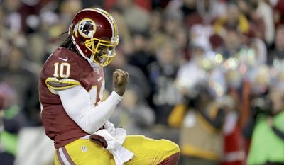 Washington Redskins quarterback Robert Griffin III (10) reacts to full back Darrel Young's touchdown during the second half of an NFL football game against the Philadelphia Eagles in Landover, Md., Saturday, Dec. 20, 2014. (AP Photo/Mark Tenally)