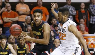 Maryland guard Jared Nickens (11) drives past Oklahoma State guard Jeff Newberry (22) in the second half of an NCAA college basketball game in Stillwater, Okla., Sunday, Dec. 21, 2014. Maryland won 73-64. (AP Photo/Sue Ogrocki)