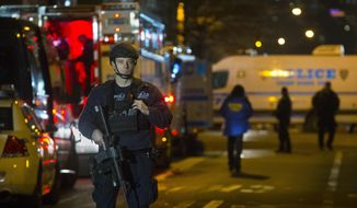 Police guard the scene where two NYPD officers were shot, Saturday, Dec. 20, 2014, in New York.  An armed man walked up to two New York Police Department officers sitting inside a patrol car and opened fire Saturday afternoon, killing both officers before running into a nearby subway station and committing suicide, police said. (AP Photo/John Minchillo)