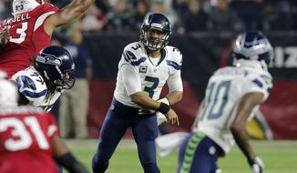 Seattle Seahawks quarterback Russell Wilson (3) throws against the Arizona Cardinals during the first half of an NFL football game, Sunday, Dec. 21, 2014, in Glendale, Ariz. (AP Photo/Rick Scuteri)