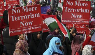 Supporters of Pakistan Awami Tehreek hold up posters to condemn Tuesday's Taliban attack on a military-run school in Peshawar, as they participate in a rally Sunday, Dec. 21, 2014 in Lahore, Pakistan. The school massacre on Tuesday horrified Pakistanis across the country. The militants, wearing suicide vests, climbed over the fence into a military-run school, burst into an auditorium filled with students and opened fire. The bloodshed went on for several hours until security forces finally were able to kill the attackers. (AP Photo/K.M. Chaudary)