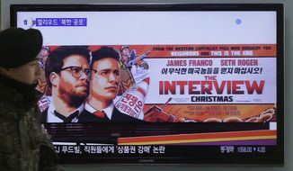 "A South Korean army soldier walks near a TV screen showing an advertisement of Sony Picture's ""The Interview,"" at the Seoul Railway Station in Seoul, South Korea, Monday, Dec. 22, 2014. (AP Photo/Ahn Young-joon)"