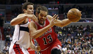 Chicago Bulls center Joakim Noah (13) drives past Washington Wizards forward Kris Humphries during the first half of an NBA basketball game, Tuesday, Dec. 23, 2014, in Washington. (AP Photo/Alex Brandon)