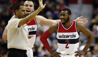 Washington Wizards center Marcin Gortat, left, and guard John Wall (2) discuss a call with referee Bennie Adams in the first half of an NBA basketball game against the Chicago Bulls, Tuesday, Dec. 23, 2014, in Washington. The Bulls won 99-91. (AP Photo/Alex Brandon)